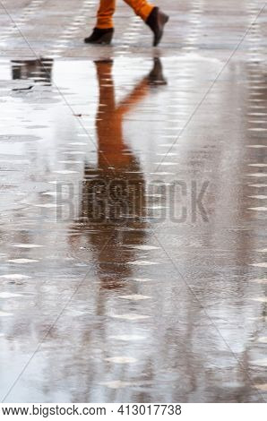 People Walking On The Street. Reflection In Water. Real People.