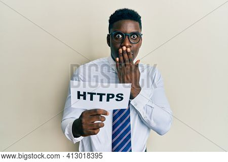 Handsome black man holding https privacy url covering mouth with hand, shocked and afraid for mistake. surprised expression