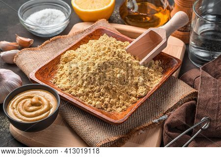 Ingredients for making mustard. Mustard powder, water, spices and ready-made mustard on a brown background. Close-up, side view.