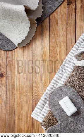 Accessories For Visiting The Bath Or Sauna On A Wooden Background: Towel, Bath Mat, Felt Hat, Washcl