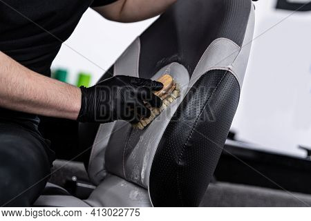 Man Car Wash Worker Cleaning Leather Boat Seat With Brush