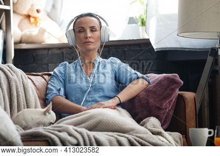 Leisure time concept. Happy beautiful woman listening to the music using headphones sitting on a couch indoors. Female spending her free day and relaxing at home alone with dog on her laps