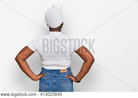 Young african woman with turban wearing hair turban over isolated background standing backwards looking away with arms on body