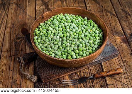 Frozen Green Peas With Ice In A Wooden Plate. Wooden Background. Top View