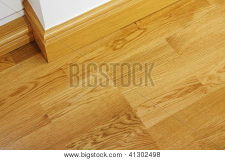 Close up showing some laminate flooring and mdf imitation wood skirting boards in newly constructed house poster