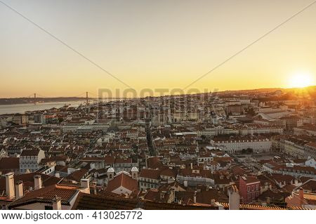 Beautiful Yellow Sunset In Lisbon, Portugal. Sun Rays Over Red Rooftops. Traveling Seatination. Roma