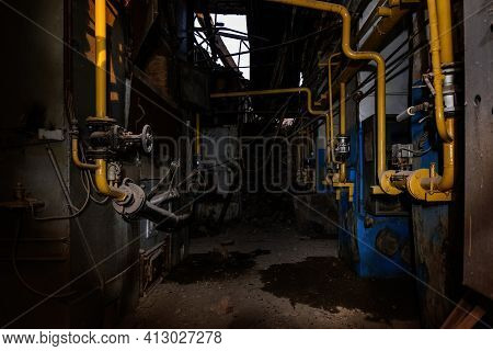 Inside Old Collapsed Industrial Building. Old Rusty Pipeline
