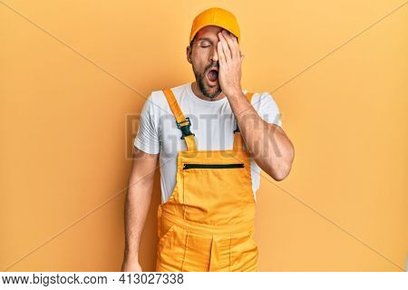 Young handsome man wearing handyman uniform over yellow background yawning tired covering half face, eye and mouth with hand. face hurts in pain.