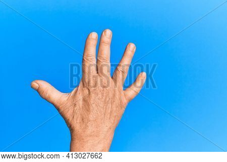 Hand of senior hispanic man over blue isolated background greeting doing vulcan salute, showing back of the hand and fingers, freak culture