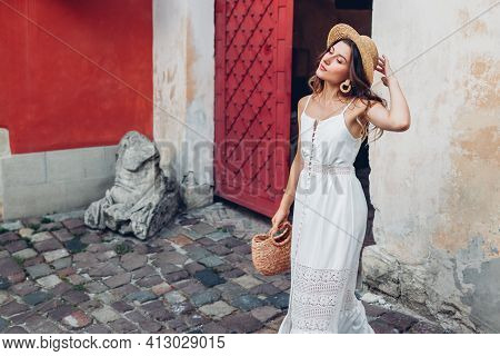 Outdoor Portrait Of Young Woman Wearing Stylish White Summer Dress And Accessories In Old Lviv City.