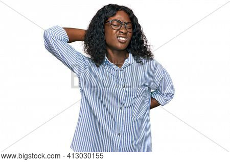 Beautiful african young woman wearing casual clothes and glasses suffering of neck ache injury, touching neck with hand, muscular pain