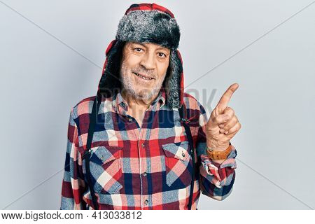 Handsome mature man wearing winter hat with ear flaps smiling happy pointing with hand and finger to the side
