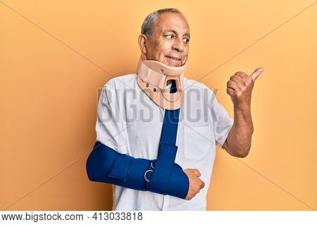 Handsome mature senior man wearing cervical collar and arm on sling smiling with happy face looking and pointing to the side with thumb up.