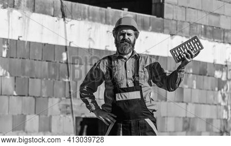 Builder Hold Brick. Bearded Man Wear Hard Hat At Construction Site. Brick Building Material Used To