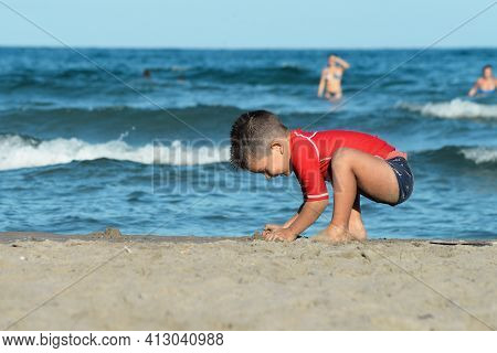 Little Boy In A Bright Red Sports T-shirt Plays In The Sea Sand , Against The Background Of Sea Wave