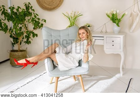 Professional Makeup Artist With A Makeup Brush In Hand. A Beautiful Woman In Red Shoes Is Sitting In