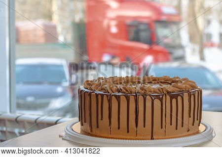 Delicious Chocolate Cake With Butter Cream On A Table In A Roadside Cafe On The Background Of A Wind