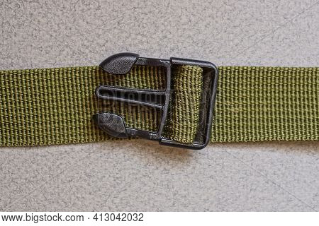 One Open Black Plastic Carabiner The Latch On The Green Fabric Harness Is On The Gray Table