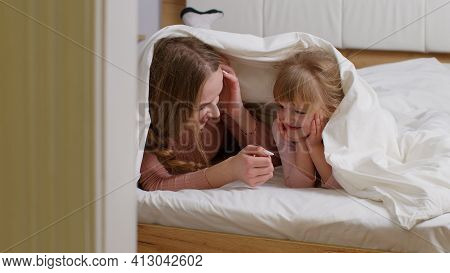 Mother Lying On Bed Under Duvet Blanket With Daughter Kid Telling Secrets To Each Other, Smilling