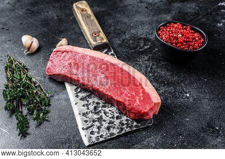Fresh Raw Top Sirloin Beef Meat Steak On A Butcher Cleaver. Dark Wooden Background. Top View