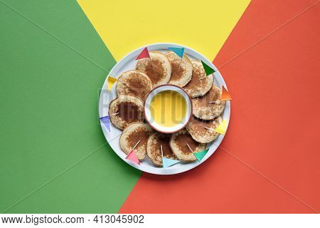 Plate Of Small Round Pancakes With Colorful Party Topper Flags On Split Three Color Layered Paper Ba