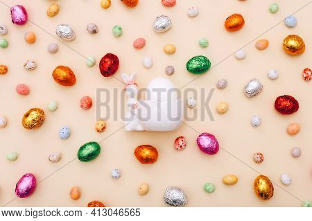 Easter Chocolate Mini Eggs And Candies Scattered On A Beige Background With Ceramic Bunny Stand For