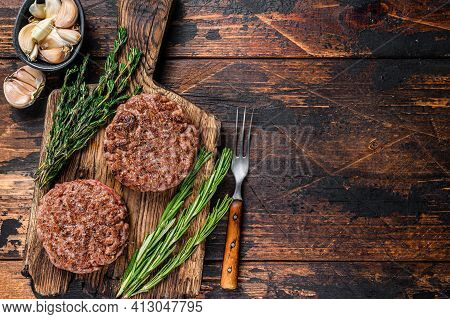 Barbecue Steak Patties For Burger From Ground Beef Meat On A Wooden Cutting Board. Dark Wooden Backg