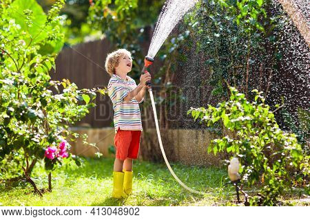 Child Watering Flowers And Plants In Garden. Kid With Water Hose In Sunny Blooming Backyard. Little