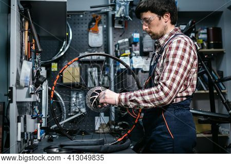 Bike Shop Mechanic Fixing Bicycle Wheel In Workshop. Serviceman Repair, Maintenance Cycle. Velociped