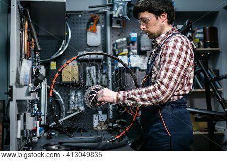 Bike Shop Mechanic Fixing Bicycle Wheel In Workshop. Serviceman Repair, Maintenance Cycle. Velociped