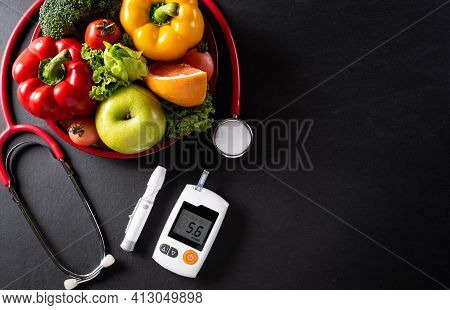 Top View Of Healthy Food In Plate With Stethoscope And Diabetes Control On Dark Background. World He