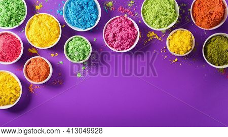 Happy Holi Festival Decoration.top View Of Colorful Holi Powder On Purple  Background With Copy Spac