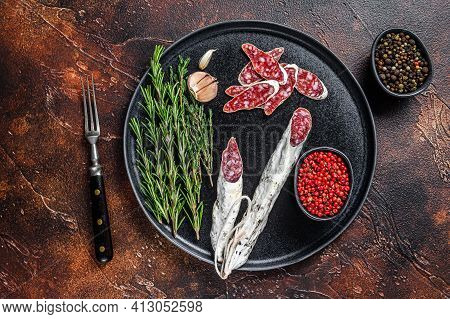 Charcuterie With Fuet Salami Sausage And Rosemary On A Plate. Dark Background. Top View