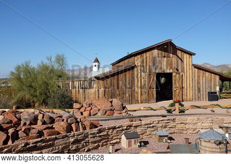 APACHE JUNCTION, ARIZONA - DECEMBER 8, 2016: Apacheland Barn and Model Railroad with the Elvis Memorial Chapel in the background at the Superstition Mountain Museum in Apache Junction, Arizona.