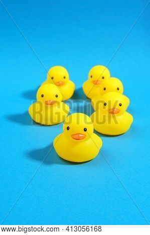 Yellow Rubber Ducks On A Blue Background. Minimal Design. Vertical Photo