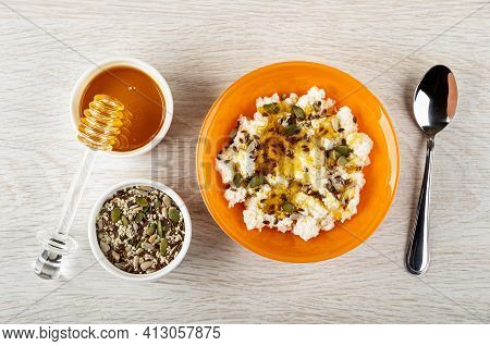 Honey Dipper On White Bowl With Liquid Honey, White Bowl With Pumpkin Seeds, Sesame, Sunflower Seeds