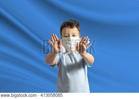 Little White Boy In A Protective Mask On The Background Of The Flag Of Somalia. Makes A Stop Sign Wi