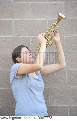 Female Trumpet Player Blowing Her Horn Against A Wall Outside.