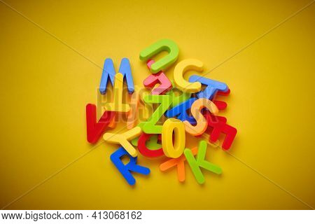 Colorful Plastic Letters Messed Up On Yellow Background. Jumble Of Letters. Dyslexia Concept