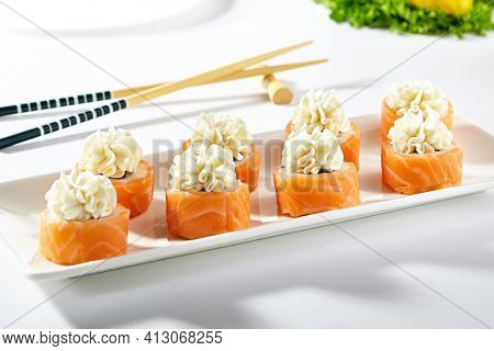 Philadelphia Sushi Roll made with Smoked Salmon. Maki sushi topped with cream cheese. White plate with wooden chopstick on white table