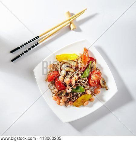 Soba noodles with seafood and vegetable. Asian style noodles food on white background. Soba in white plate with wooden choopsticks. Top view