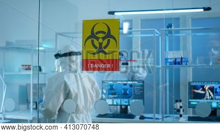 Scientist Team In Protective Suit Preparing Tools For Analysing Virus Development In Danger Zone Of