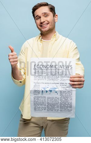 Happy Young Man In Shirt Holding Economical Newspaper And Showing Thumb Up Isolated On Blue.
