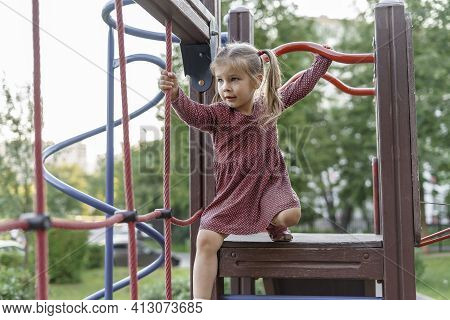 Happy Little Girl Playing On The Playground. Kid Having Fun With The Climbing Net Outdoors. Summer C