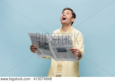 Excited Young Man In Shirt Reading Travel Newspaper Isolated On Blue.