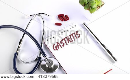 Text Gastritis On A White Background With Pills And Stethoscope. Medical