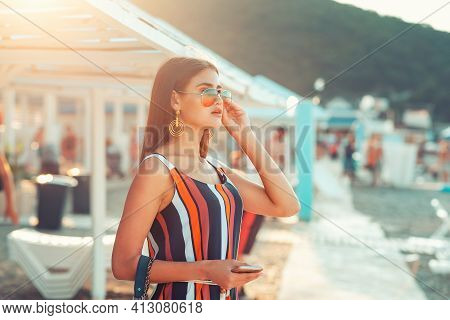Portrait Of A Beautiful Woman In Sunglasses Posing On The Beach. Sun Beds And Umbrellas Are In The B