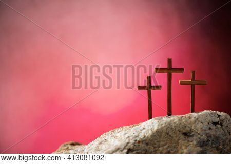 Crucifixion, Resurrection Of Jesus Christ. Three Crosses Against Red Sky On Calvary Hill Background.