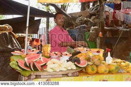 A Man Selling Fresh Prepared Fruits Cut In Pieces In His Street Food Stall On Fruit Stall Cart Durin