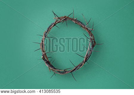Crown Of Thorns On Green Background. Top View. Copy Space. Christian Easter Concept. Crucifixion Of